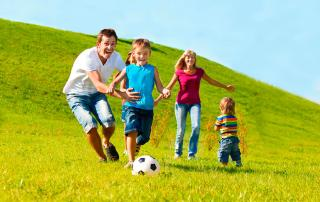 Parents play soccer with kids